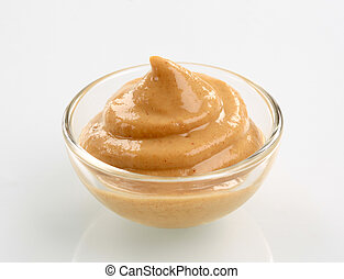 Swirl of spicy mustard in a small glass bowl