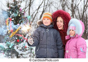 mutter, und, sie, zwei kinder, gleichfalls, stehende , bei, christmass, baum, und, anschauen, bengal, licht, in, jungen, hand., christmass, baum, in, heraus, von, fokus.