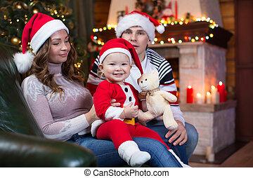 mutter, vater, und, baby- junge, in, santa, rotes kleid, lächeln, auf, a, hintergrund, von, weihnachtsbäume, in, der, inneneinrichtung, von, der, haus