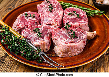 Mutton lamb neck meat on a rustic plate with thyme and rosemary. wooden background. Top view