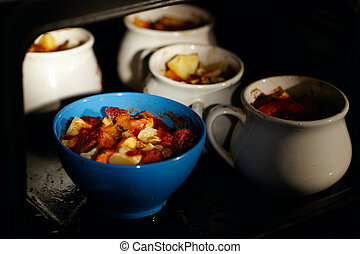 Mutton meat and potatoes, baked in pot.