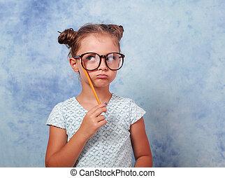 myślenie, grimacing, koźlę, dziewczyna, w, okulary, przeglądnięcie do góry, i, mieć, na, idea, dzierżawa, ołówek w ręce, na, błękitne tło, z, opróżniać, kopiować przestrzeń