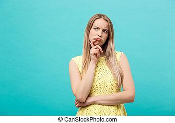 myślenie, młody, zaufany, kobieta, w, żółty strój, przeglądnięcie do góry, odizolowany, na, błękitne tło