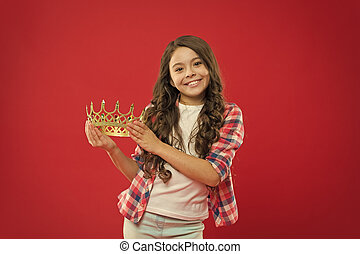 My biggest treasure. Kid hold golden crown symbol of princess. Childhood concept. Every girl dreaming to become princess. Girl cute baby hold crown while stand red background. Lady little princess
