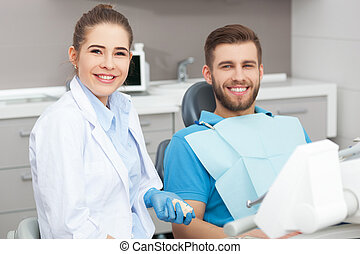 Portrait of a female dentist and young man in a dentist office.