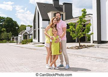 Joyful pleasant man hugging his wife and daughter