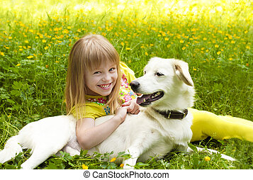 Little beautiful girl hugging her dog in the summer of nature.