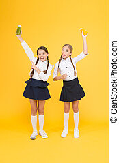 My favourite food. happy classmates in school uniform. back to school. little girls hold healthy juice or yoghurt. lunch time on school break. pupils on yellow background. friendship concept