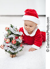 My first christmas - baby girl with small decorated tree