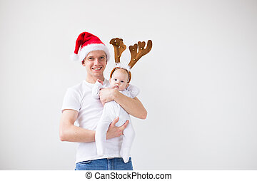 My first Christmas. Dad in santa hat holding his baby girl daughter wearing in deer horns on white background with copy space