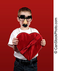 A little boy with fake nose and glasses offering a box of Valentines candy.