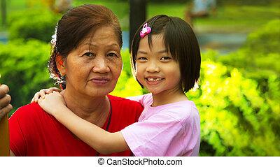 My Grandma - Grand daughter hugging Grandmother in the park.