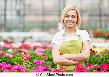 My job is my passion. Beautiful young woman in apron keeping arms crossed and smiling while standing in a greenhouse