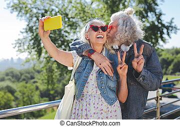 Joyful happy man kissing his wife