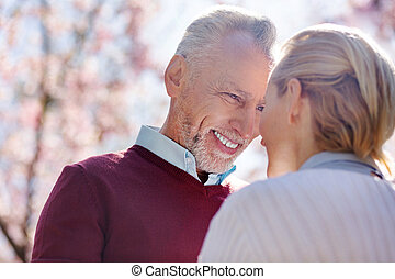 Happy cheerful man smiling to his wife