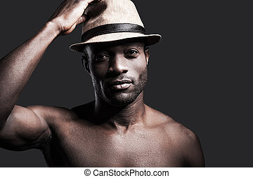 My lucky hat. Portrait of young shirtless African man adjusting his hat and looking at camera while standing against grey background