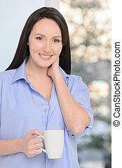 My morning starts with coffee. Beautiful middle-aged woman standing in front of the window holding a cup