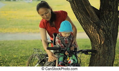 My mother takes care of a beautiful baby boy in a bicycle seat in the park