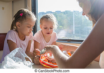 My mother unpacks the food for hungry children in second-class train carriage