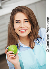 Portrait of happy patient in dental chair with green apple.