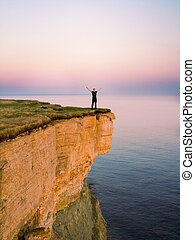 my world - young man standing on a cliff with raised hands