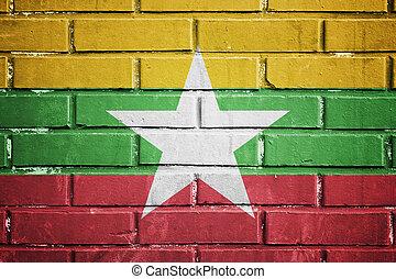 Myanmar flag on a textured brick wall