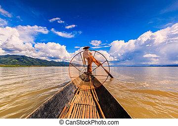 Myanmar Inle lake fisherman on boat catching fish by...