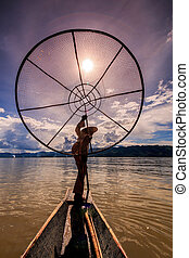 Myanmar Inle lake fisherman on boat catching fish by traditiona