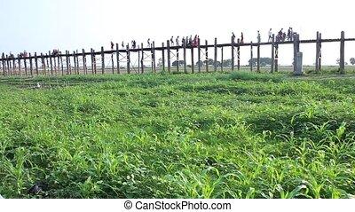 People walk at U Bein Bridge longest teakwood bridge in the world