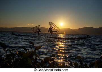 Myanmar, Shan state, Inle lake Intha fisherman on boat at amazing sunset