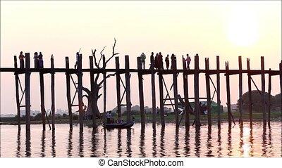 Silhouette life of Ubein Bridge at sunrise, Mandalay, Myanmar, Handheld record on boat