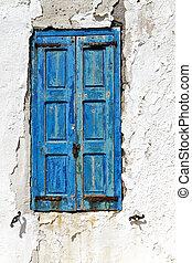Mykonos island in Greece - Old window with blue shutters...