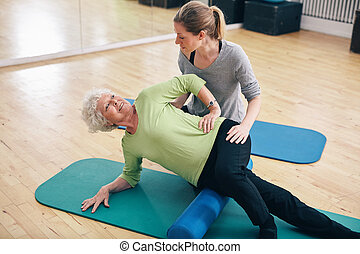 Physical therapists assisting senior woman to perform myofascial release technique with a foam roller to inhibit overactive muscles at gym.