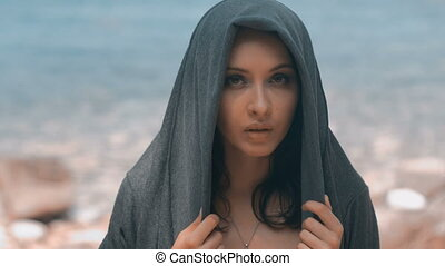 Mysterious beautiful woman with make up in grey hood