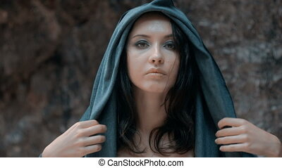 Mysterious beautiful woman with make up puts on her hood