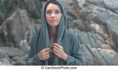 Mysterious beautiful woman with make up takes off her hood