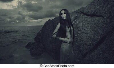 Beautiful mysterious woman in long dress at the sandy beach near rocks over sea and cloudy sunset sky background - black and white video in slow motion