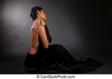 Mysterious beauty - Beautiful woman sitting on black ...