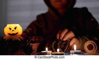 Mysterious Boy with in Hood Performs Rite by Candle in Dark Room on Halloween. Silhouette of Boy. Creepy, dark mysterious night ambiance. Concept of children's party. Decorations with a pumpkin. 4K