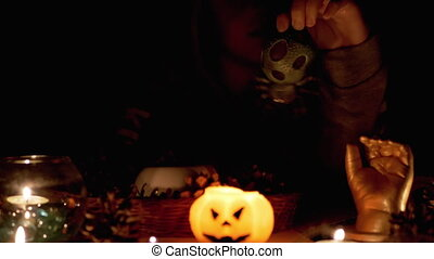 Mysterious Boy with in Hood Performs Rite by Candle in Dark Room on Halloween. Silhouette of Boy. Creepy, dark mysterious night ambiance. Concept of children's party. Decorations with a pumpkin.