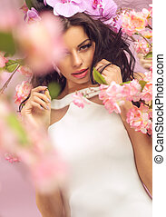 Mysterious brunette woman with lots of flowers