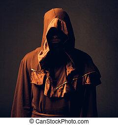 mysterious Catholic monk on dark background. studio shot