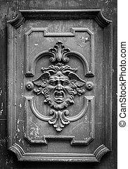 Mysterious door - Gothic mask on an old wodden door in Milan...