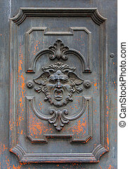 Gothic mask on an old wodden door in Milan - Italy