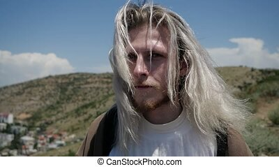 Mysterious fellow traveller with long blond hair stands in the mountains in windy weather and looks straight into the camera. High quality FullHD footage
