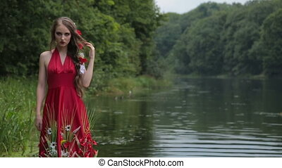 Mysterious girl with creative make-up in ethnic red dress walking in water