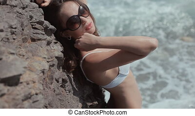 Mysterious girl with glasses and a white bikini posing near a rock in the sea