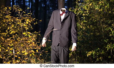 Mysterious headless figure in a business suit with a butterfly standing in the night forest on the eve of halloween. Dark entities
