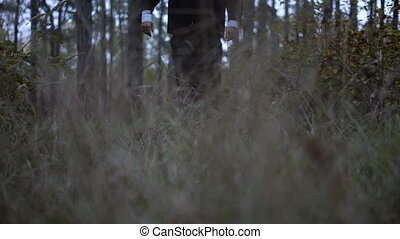 Mysterious headless figure in a business suit with a butterfly walking in the dark forest on the eve of halloween