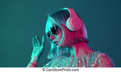 Mysterious hipster teenager listening to music with headphones. Portrait of millennial pretty girl with short hairstyle with neon light. Dyed blue and pink hair.